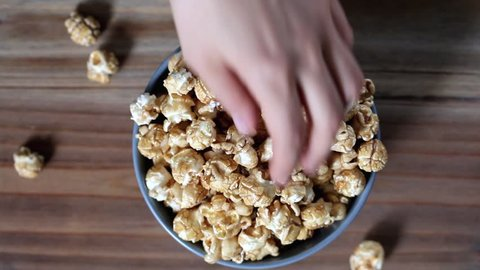 Top view of hands taking sweet caramel popcorn from a common blue bowl on a wooden table.