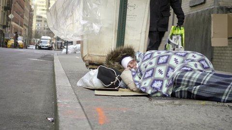 NEW YORK - MARCH 9, 2017: Homeless White Woman Sleeping In Blanket On Sidewalk In Street By Garbage 4K NYC. Each night thousands of homeless people sleep on the City's streets and other public spaces.