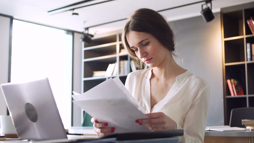 office space computer. Busy Beautiful Young Woman Work On Laptop Computer With Business Papers, Pick Up Telephone Office Space