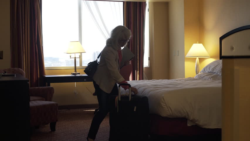 A mature female business traveler with surface tablet heads out of her hotel room with luggage in tow. | Shutterstock HD Video #26406914