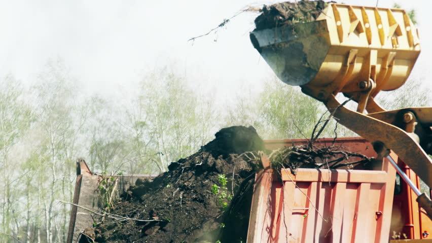 Wheel loader excavator loading construction garbage in a dump truck. 4K UltraHD video footage #26446799