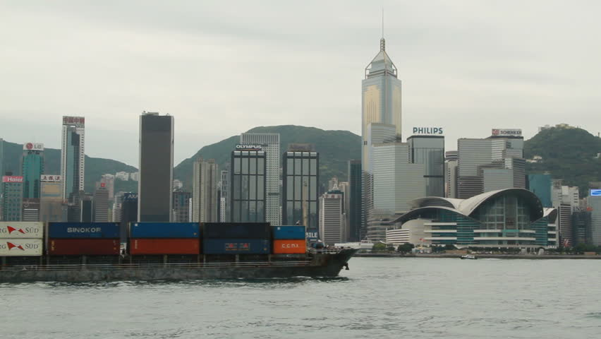 HONG KONG - MARCH 25: Container ship crossing the Victoria habour and city skyline on March 25, 2010 in Hong Kong, China.