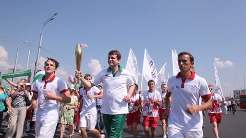 KAZAN, TATARSTAN/RUSSIA - MAY 15 2013: Happy sports competition participants run with Olympic fire torch between people against clear blue sky on May 15 in KAZAN