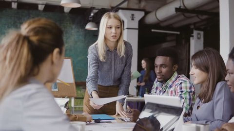Blonde woman team leader giving direction to mixed race team of young guys. Creative business meeting at modern office.