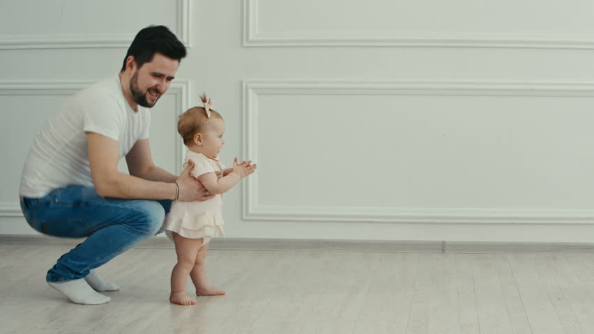 Family portrait. Father teaches his little daughter to walk