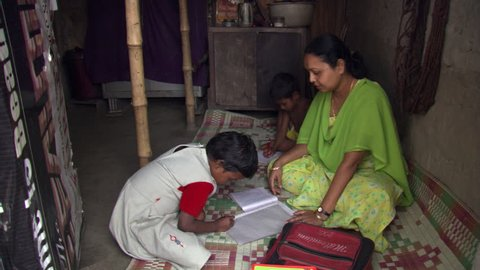 Mother and children doing schoolwork in Calcutta home