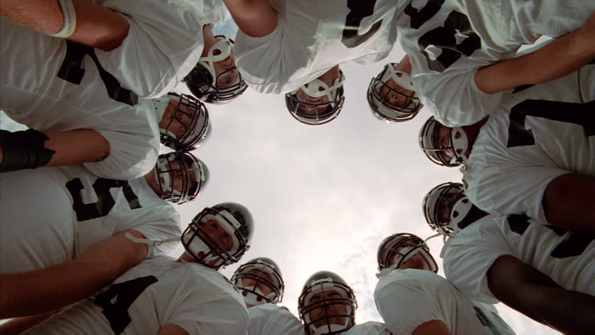 Football players in a huddle, camera looking up from center