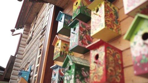 Colorful bird houses. Handmade wooden birdhouse on log house. Birdhouses on the wall. Neighborhood. Wooden birdhouse in vintage style