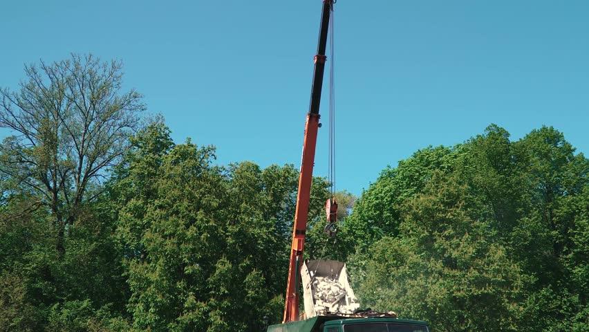 Crane Unload broken bricks to a truck. garbage #26536757