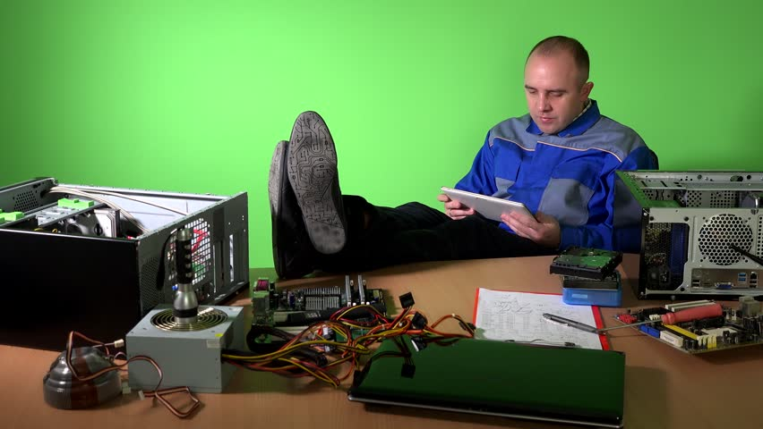 Careless engineer man with legs on table playing with tablet. Lot of broken computer parts on desk at pc repair shop. Green wall background. Static shot. 4K UHD