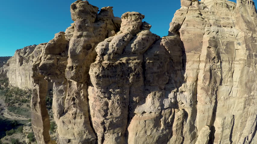 Aerial-Flying over rugged sandstone monolith of Eagle Canyon Arch reveals fortress-like rock formation in the San Rafael Swell desert beyond on a sunny day with a clear blue sky