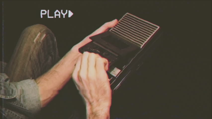 Fake VHS tape: a man inserts a tape into a cassette player and hits the record button.