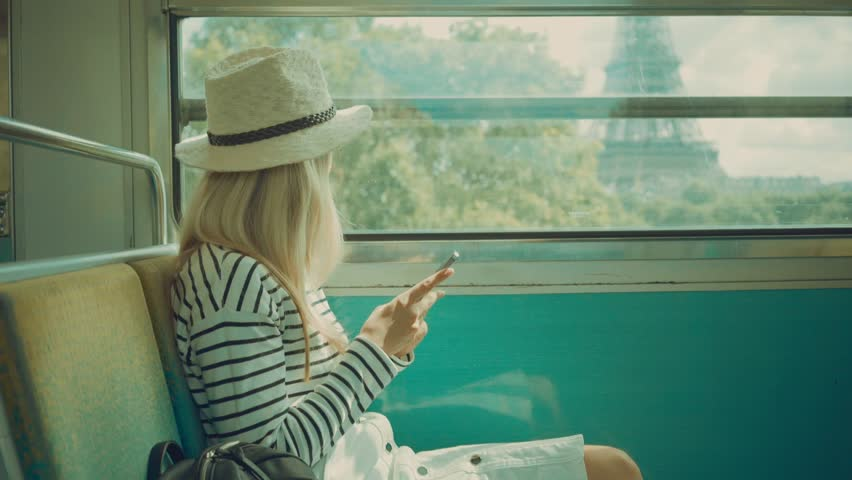 Woman tourist sitting at train and looking to mobil phone near the Eiffel tower at sunny day in Paris. Famous popular touristic place in the world. | Shutterstock HD Video #26607374