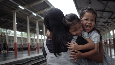 Two cute asian little girls are running to give a hug with their mother on railway station