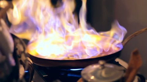 Chef making bananas foster in a metal pan.