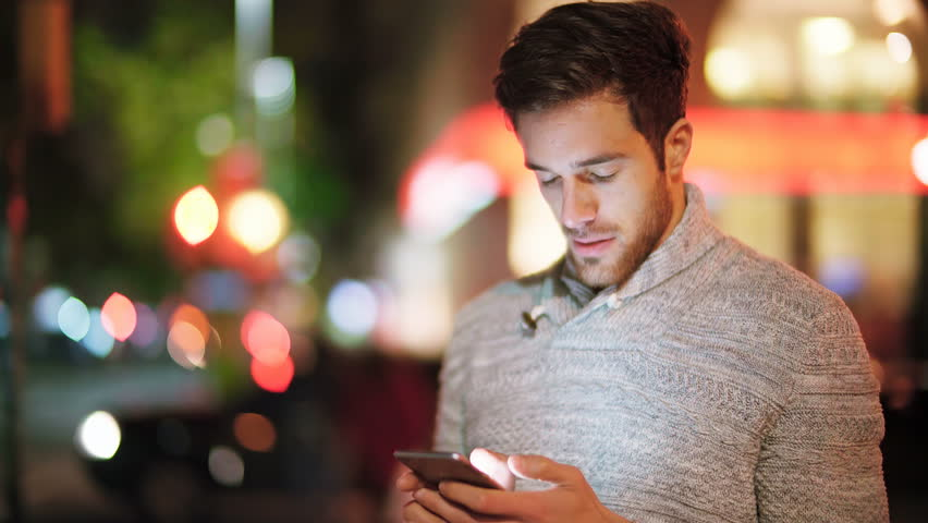 Handsome young man using smartphone in a crowded street. He is checking mails, chats or the news online. Night. Crowded street.