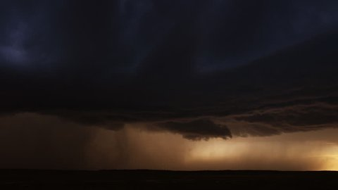 Lightning flashes from a black cloud dropping a curtain of rain on a dark prairie, time lapse