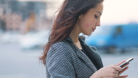 Side-view closeup of youthful tender business girl in strict gray jacket and black dressstaying on the busy urban streetand using her smartphone Steadicam slow motion shot