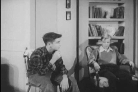 1940s: A student reads a quotation and his friend corrects her report, in 1949.