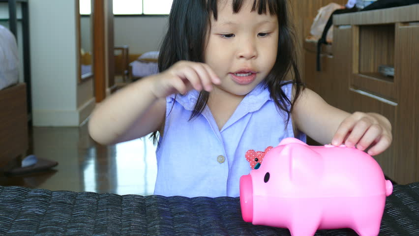 Cute little girl putting money in piggy bank