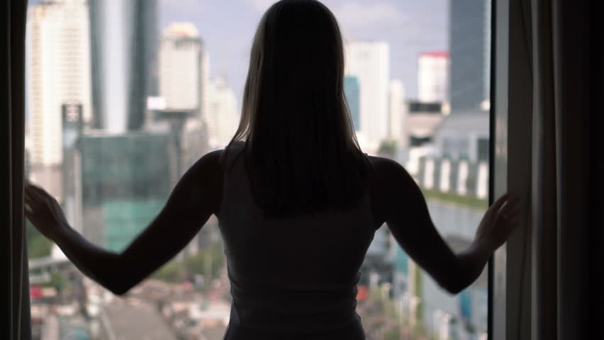 Silhouette of woman unveiling curtains and looking out of window. City skyscrapers landscape outside