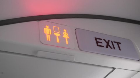 Shot of airplane lavatory sign turning from green (available) to red (occupied). Beside the lavatory sign is an exit sign.