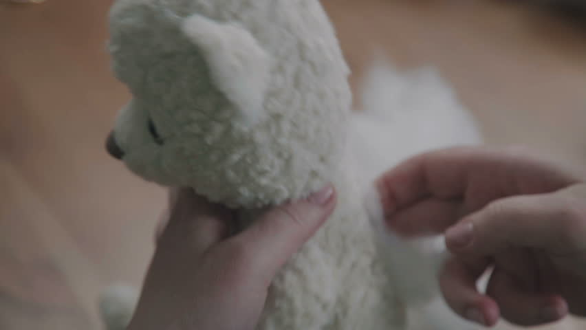 Repair of plush toys: female hands sew a teddy bear. Creating soft handmade toys. Broken toy vintage bear cub - restoration of an old toy. Sew a soft toy