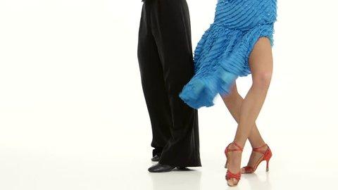 Legs of couple elegant ballroom dancers perform rumba, white background