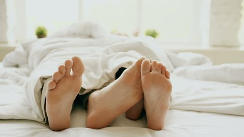 Closeup of young beautiful and loving couple hug and play their feet each other under blanket while wake up in bed in morning