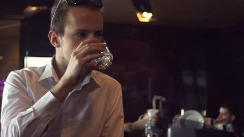 SLOW MOTION: Handsome young man sipping drink in a bar. Lifestyle concept.