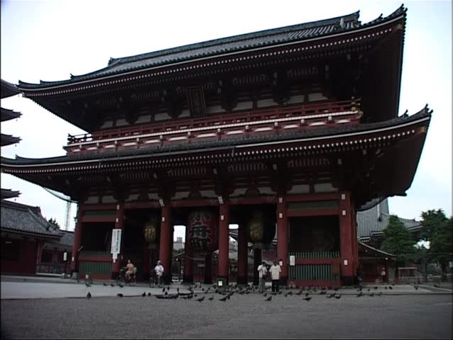 TOKYO, JAPAN - CIRCA JUNE 2003 - Buddhist temple Asakusa Kannon, also known as Sensoji, with Mum and son passing on a bike.