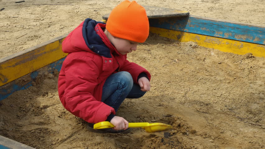 kid play with children's shovel in sandbox