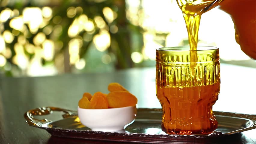 Man pouring Qamar El Din (Apricot Juice) into a glass , ready for happy breakfast in Ramadan