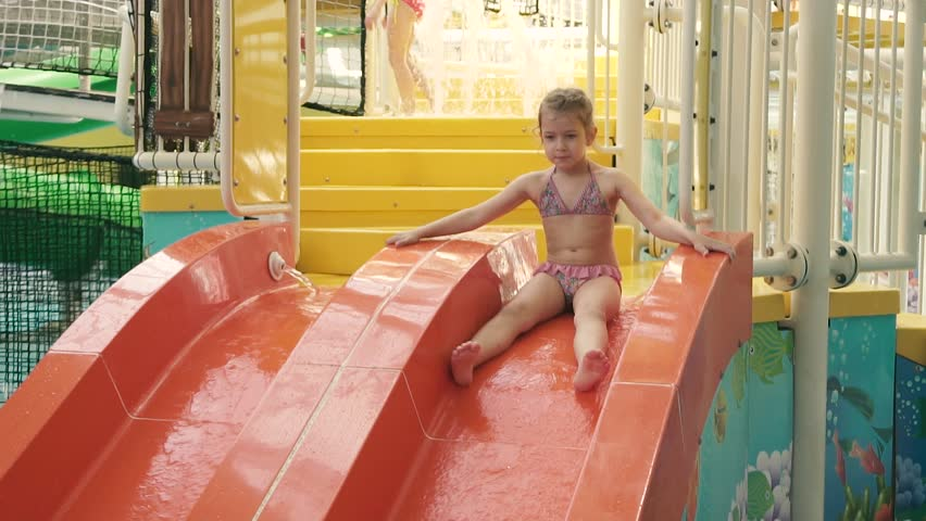 80bd32097ddd8 Little girl is riding a slide in a water park. slow motion