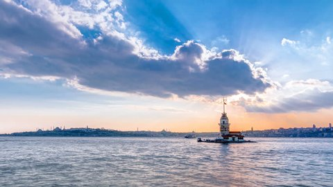 Maidens tower before sunset with colorful clouds and rays of sun light timelapse in istanbul, turkey, kiz kulesi tower. City skyline on background with reflection on Bosforus water