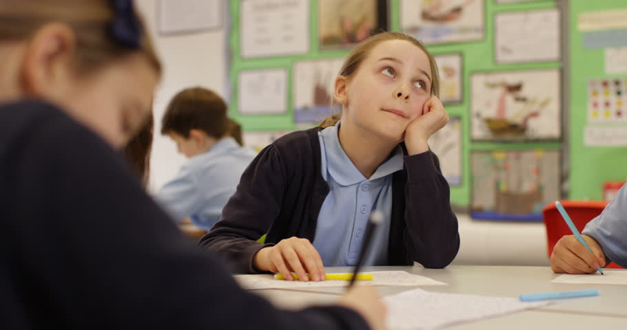 4K Portrait of bored little girl in school classroom daydreaming at her desk. Slow motion