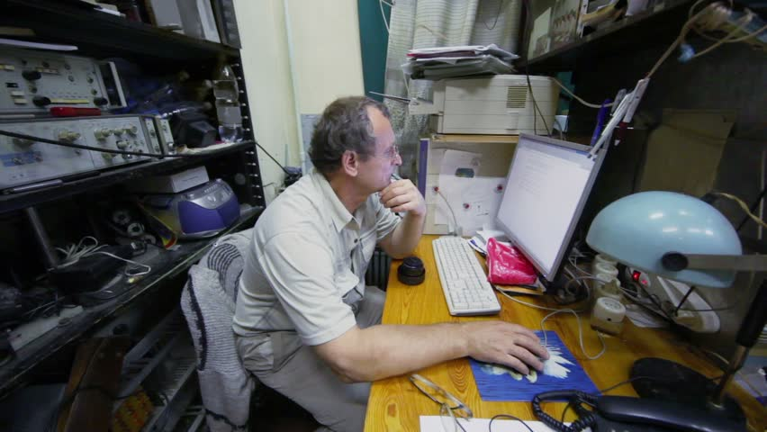 Man sit at table and watch display of computer in room with equipment on shelves