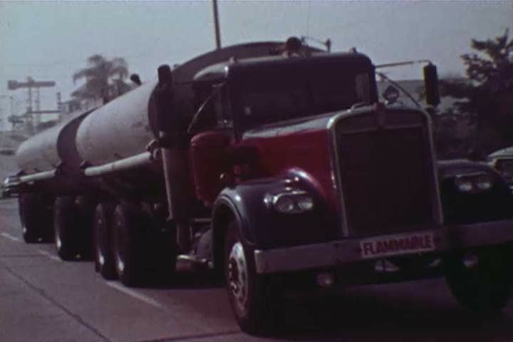 1970s: Gasoline tanker trucks are driven and drivers fill up their cars at a service station, amidst congestion and smog, in Santa Barbara, California, in 1971. | Shutterstock HD Video #26826364