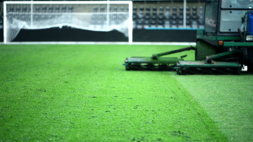 Cutting grass in a football stadium with mowing equipment