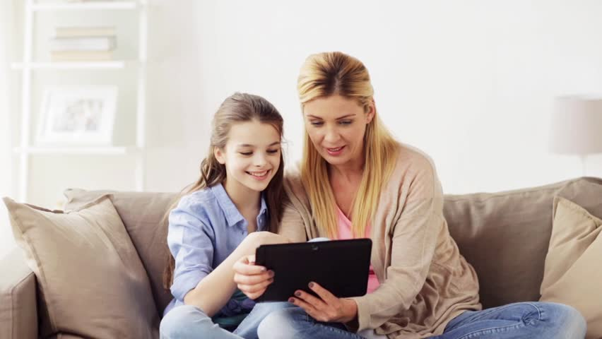 people, family and technology concept - happy girl and mother with tablet pc computer at home