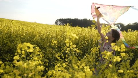 Sunset shot of cute teenager girl wears dress plays with flying colorful kite, runing on field of yellow flowers, freedom concept, 120FPS slowmotion