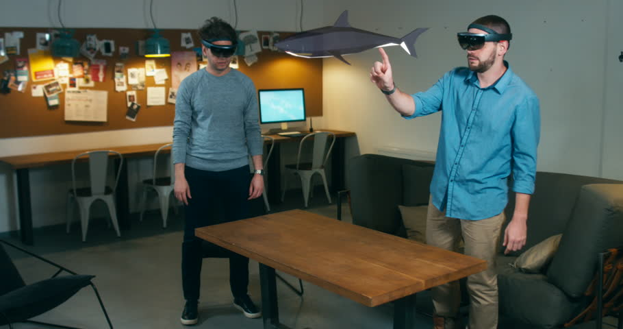 Young adult Caucasian colleagues using holographic augmented reality glasses together, discussing shark model hologram. Game development. 4K UHD RAW edited footage