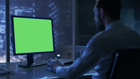 Late at Night Businessman Works on a Personal Computer with Green Mock-up Screen in His Private Office with Big City Window View.