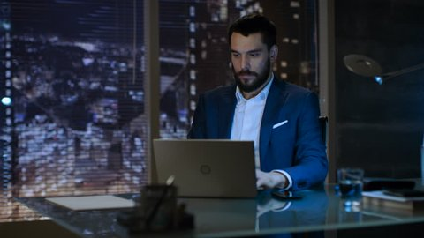 Businessman Works on a Laptop in His Private Office with Big City Window View.