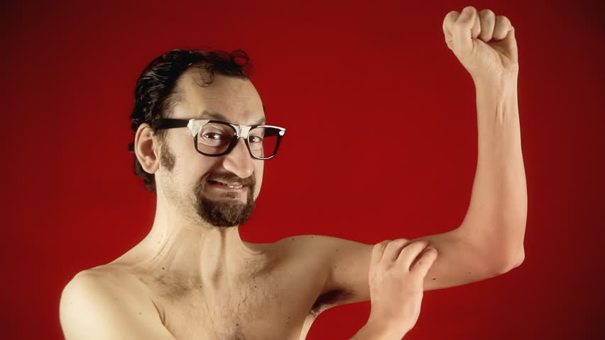 A funny ugly slim nerd man, showing the strength of his muscles by flexing them, half naked.