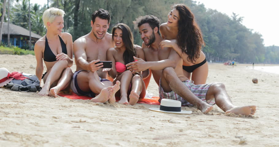 People Sit On Beach Use Cell Smartphone Talking, Young Happy Man And Woman Group On Vacation Communication Tourists On Summer Holiday Slow Motion 60 | Shutterstock HD Video #26946496