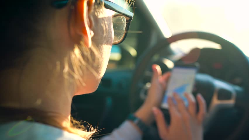 Woman in glasses using a smartphone in the car | Shutterstock HD Video #26957794