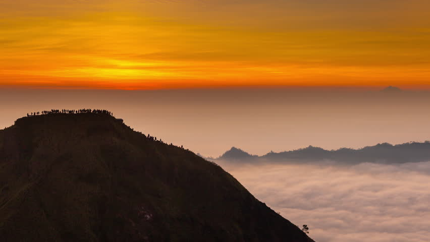 One of the main attractions of the tropical island of Bali - Active volcano Batur hiking travelers tourist visited at dawn to meet the beautiful sunrise on the top of mountain / Bali, Indonesia