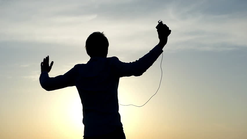 Young Fair Haired Man With a Crew Haircut is Dancing Energetically, Rasing His Hands by Turns, While Listening to Music From His Smartphone With Black Earbuds in His Ears at a Nice Sunset Not Far #26965474