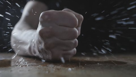 The man beats his fist on the wet table showing aggression. Concept of cruelty.